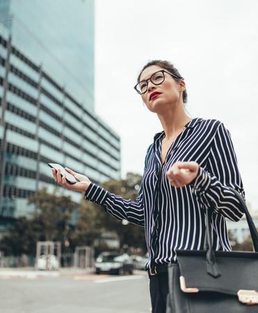 女性ビジネス エグゼクティブ保有携帯電話、タクシーを呼ぶします。街の通りでタクシーを待っているアジアの実業家。