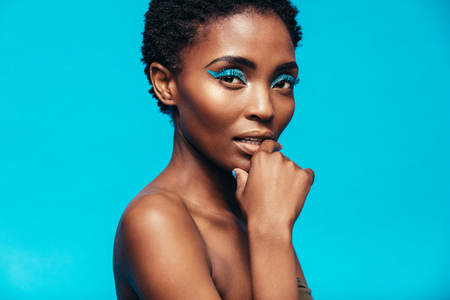 青い背景にメイクと官能的なアフリカ女性モデルのクローズ アップ。鮮やかな化粧品カメラ目線で若い女性。