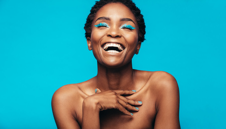 Close up of cheerful young woman with blue eye shadow makeup. Beauty portrait of female model with vivid makeup laughing on blue background.