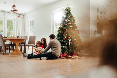 Familia sentada cerca de cajas de regalo de apertura de árbol de Navidad. Joven pareja ayudando a su hija a abrir regalos de Navidad. Foto de archivo