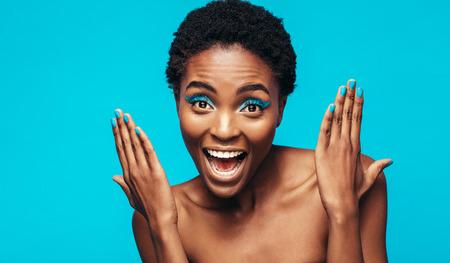 ブルーのアイシャドウを持つ女性のクローズ アップと背景に青い塗料を爪します。彼女の鮮やかなメイクを見せて興奮の女性モデル。