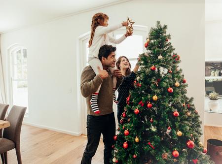 Família decorar uma árvore de Natal. Jovem com a filha nos ombros, ajudando-a a decorar a árvore de Natal.