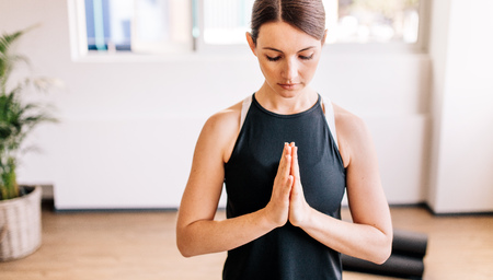 manos unidas: Fitness female meditating with her eyes closed and hands joined indoors. Woman in easy posture with Namaste, meditating, breathing and relaxing.