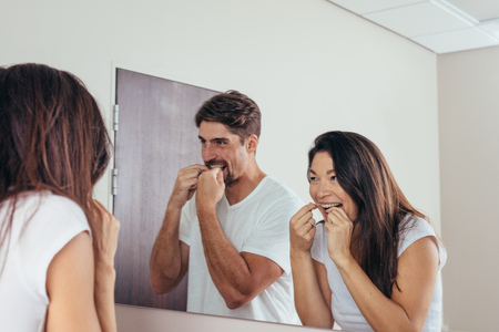 Couple looking in the mirror and smiling, using dental floss to clean their teeth. Man and woman brushing teeth together in bathroom in morning. Stock Photo