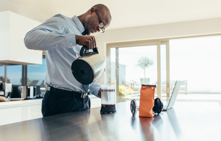 Man pouring hot water in coffee maker. Businessman preparing coffee on breakfast table with a laptop computer by the side. Stock Photo