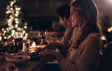 Bella giovane donna che si siede con la famiglia e cena di Natale. Famiglia che celebra il Natale insieme a casa.