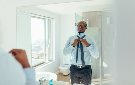 Businessman wearing a tie looking at the mirror. Man dressing up looking at the mirror in bathroom.