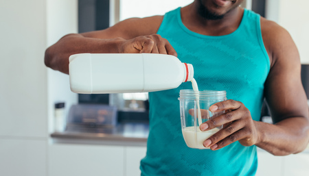 Man pouring milk in a glass after workout. Young man in kitchen preparing breakfast. Stock Photo - 88273933