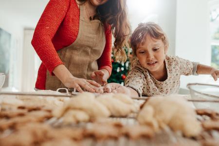 Moeder en kind maken kerstkoekjes. Dochter die koekjesdeeg plaatsen op bakseldienblad terwijl moeder koekjes met snijder snijdt.