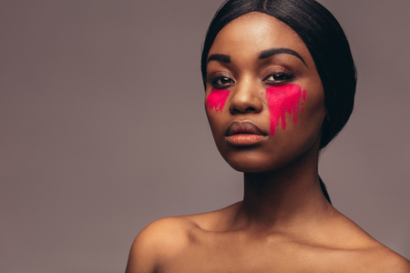 African woman with dramatic eye makeup. Portrait of female model looking at camera with serious expression. Imagens