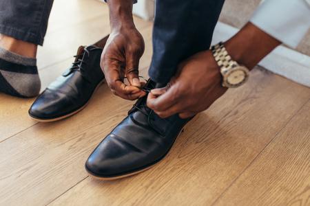 Close-up van een zakenman bindende schoenveters. Man met formele schoenen.