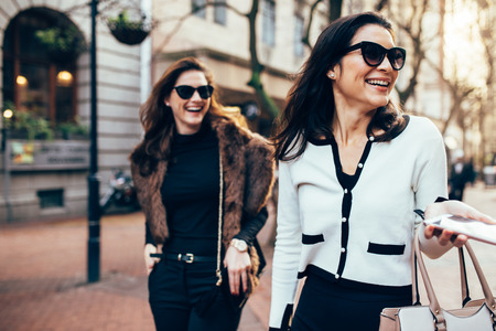 재미 거리 도시의 두 여자입니다. 도로 아래로 산책하고 야외에서 웃는 여자 친구. 스톡 콘텐츠