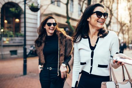 Due donne sulla strada cittadina divertendosi. Amici femminili sulla camminata giù la strada e sul sorridere all'aperto. Archivio Fotografico