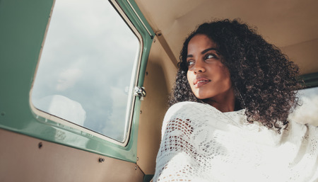 African woman on road trip traveling in a van. Thoughtful woman sitting inside the van and looking outside the window. Stock Photo
