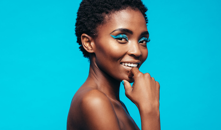 Close up of woman with makeup smiling against blue background. African female model with vivid makeup.