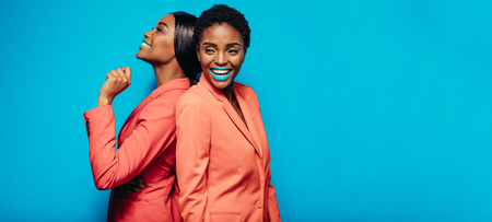 Happy female friends standing back to back against blue background. Two woman fashion model in stylish clothing and vibrant makeup. 写真素材