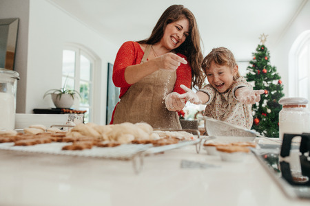Happy mother and daughter playing with cookie flour at kitchen table while making Christmas cookies. Baked cookies and muffins on the kitchen table for Christmas.