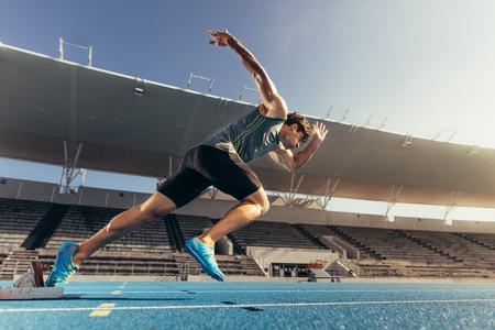 Läufer, der Startblock verwendet, um seinen Lauf auf der Laufbahn in einem Stadion zu starten. Athlet startet seinen Sprint auf einer Allwetterlaufbahn.