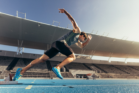 Runner using starting block to start his run on running track in a stadium. Athlete starting his sprint on an all-weather running track. Zdjęcie Seryjne - 89305145