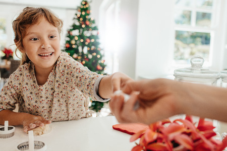 Happy little girl making Christmas cookies on kitchen table. Girl using moulds and shape cutters to make cookies.