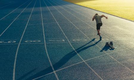 Athlet läuft allein auf einer Allwetterlaufbahn. Läufer sprintet auf einer blauen, gummierten Laufbahn, beginnend mit einem Startblock. Standard-Bild