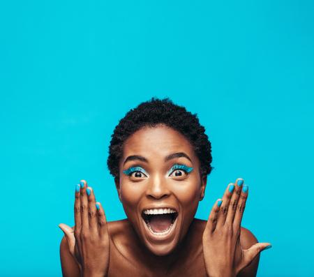Opgewonden jonge vrouw met levendige oogschaduw en spijkerverf. Vrouwelijk model dat haar levendige make-up toont tegen blauwe achtergrond.