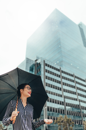 Young woman standing outdoors in the city holding umbrella and smiling. Urban female professional smiling on the city street with umbrella.