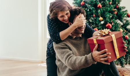 Bedeckungsaugen der jungen Frau ihres Partners bei der Übergabe eines Weihnachtsgeschenks. Junge Paare, die glückliche Momente beim Weihnachten zu Hause feiern verbringen. Standard-Bild - 88908526