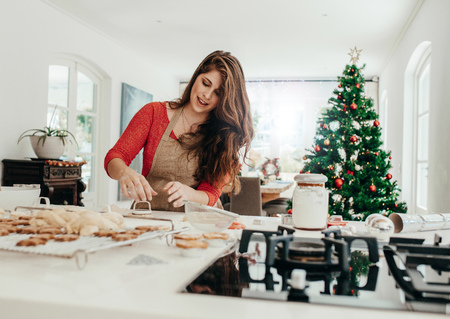Young woman making shaped cookies with cutter for Christmas. Living room decorated with Christmas tree in the background.