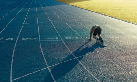 Achtermening van een atleet klaar om op een spoor geschikt voor alle weersomstandigheden te sprinten. Runner met behulp van een startblok om zijn run op het circuit te starten.
