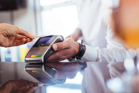 Main de client payant avec carte de crédit sans contact avec technologie NFC. Barman avec une machine de lecteur de carte de crédit au comptoir avec femme tenant une carte de crédit. Concentrez-vous sur les mains. Banque d'images