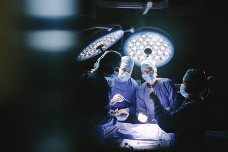 Group of surgeons in operating theater. Medical team performing surgery in operation room.