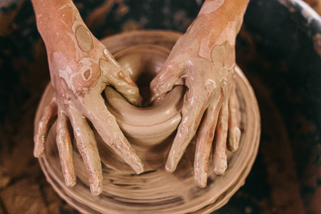 moulding: Potter making a clay pot on pottery wheel in workshop. Close up of hands of craftswoman moulding clay on pottery wheel.
