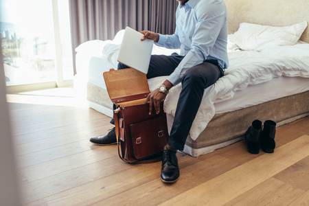Businessman putting his laptop in bag. Man getting ready to go to office.