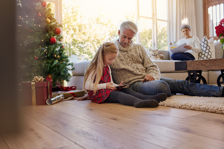 Little girl with grandfather sitting on floor and using digital tablet during Christmas, with grand mother sitting on sofa at the back. Little girl and grand parents in living room during christmas.