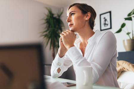 Woman sitting at her desk in office thinking deeply. Business woman sitting in office with chin resting on hands looking away.