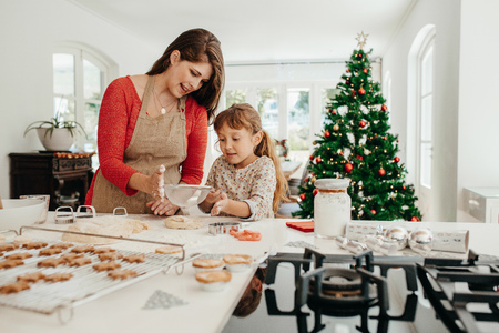 Mother teaching her daughter to make cookies. Little girl sifting flour for making cookies. Stock Photo