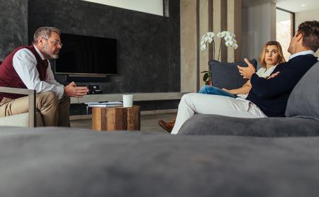 Psicólogo masculino ouvir casal durante a sessão. Marido e mulher conversando com o psicoterapeuta, compreendendo as dificuldades na vida conjugal. Foto de archivo - 89712601