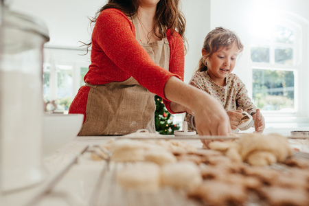 Mother and daughter making Christmas cookies. Little girl using a mould to make cookies. Stock Photo