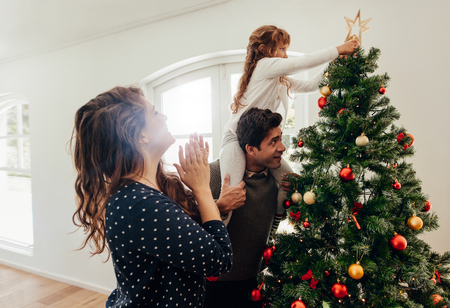 Family decorating a Christmas tree. Young man with his daughter on his shoulders helping her to place a star on Christmas tree. Stock Photo