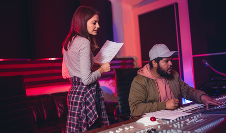 Female singer with man working on audio mixing console in recording studio. People working in professional music studio. Stock Photo