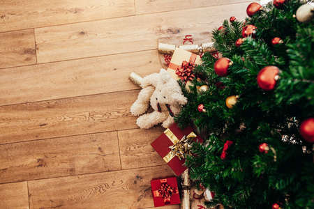 Beautifully wrapped Christmas gifts and  Christmas crackers placed beside a Christmas tree. Christmas background with decorations and gift boxes on wooden floor. 版權商用圖片 - 89713101