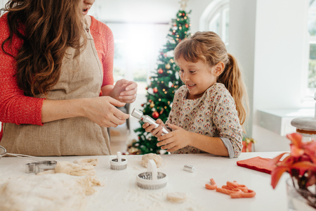 Mother and daughter pulling a Christmas cracker. Woman making Christmas cookies using dough moulds and cutters. Stock Photo
