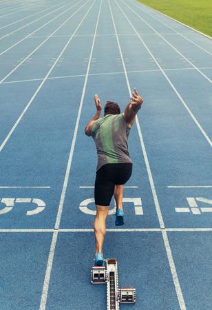 Achtermening van een atleet die zijn sprint op een looppas voor alle seizoenen begint. Runner die startblok gebruikt om zijn looppas op renbaan te beginnen.