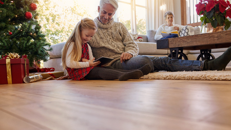Senior man with granddaughter sitting on floor using digital tablet. Little girl and grand parents in living room during christmas. Stock Photo