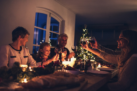 Three generation family enjoying christmas dinner together at home. Extended family toasting wine at christmas dinner. Imagens