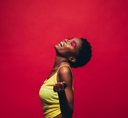 Cheerful young woman dancing over red background. African female model dancing in studio and enjoying.