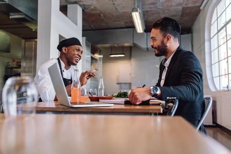 Restaurant bedrijfsleider die en met chef-kok zit spreekt. Restauranteigenaar die een gesprek met werknemer heeft.