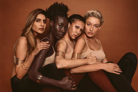 Group of diverse women sitting together against brown background. Multi ethnic females with different skin tones in studio. Stock fotó - 89789668