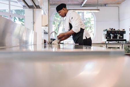 Restaurantwerknemer die een doek in water voor het schoonmaken van teller doorweken. Mens die bij commerciële keuken werkt.
